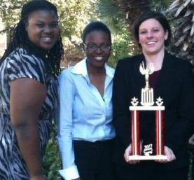 From left: Marla Cole, Angela Johnson and Dr. Allison Merrick hold a trophy after competing at the Texas Regional Ethics Bowl in San Antonio, Texas. Credit ualr.edu